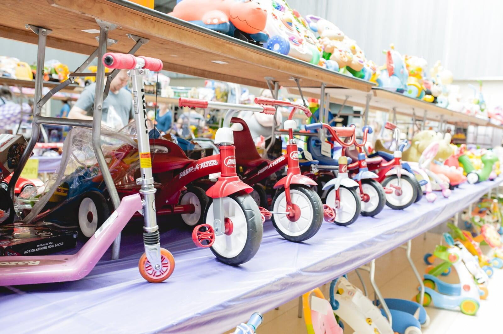 Tricycles, scooters and toys lined up on a table waiting for shoppers to attend the sale.